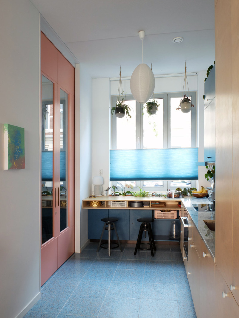 The blue kitchen with contrasting pink sliding doors - Photo by LAGADO architects